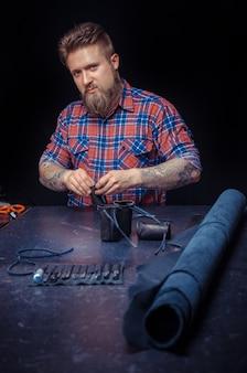 Кожевник создает новое изделие из кожи в мастерской. / художник, работающий с кожей, работает с кожаными изделиями в кожевенной мастерской.