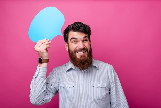 Leave a comment ! young bearded man is holding a blue speech bubble on pink background.