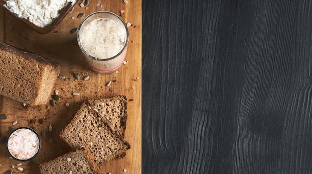 種入れぬパン、カボチャとヒマワリの種を使った全粒ライ麦パン。テーブルの上のパン種スターター。本物のサワードウパン、オーガニックバイオ製品。コピースペース、ブレッドボードのスライスを含む上面図