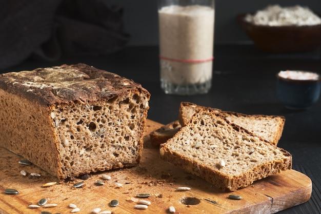 種入れぬパン、カボチャとヒマワリの種を使った全粒ライ麦パン。テーブルの上のパン種スターター。本物のサワードウ自家製パン-有機バイオ製品。手作りの製品、船上のパンのスライス
