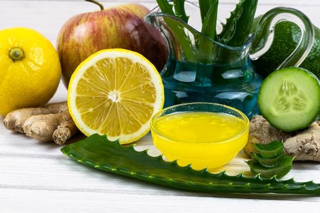 白い木製の背景にガラスの水差しにアロエ、レモン、リンゴと生姜、キュウリ、ジュースアロエから栄養マスクを残します。