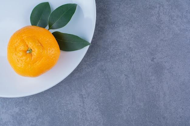 Листья и сочные апельсины на тарелке на мраморном столе.