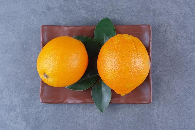 Листья и сочные апельсины на деревянной тарелке на мраморном столе.