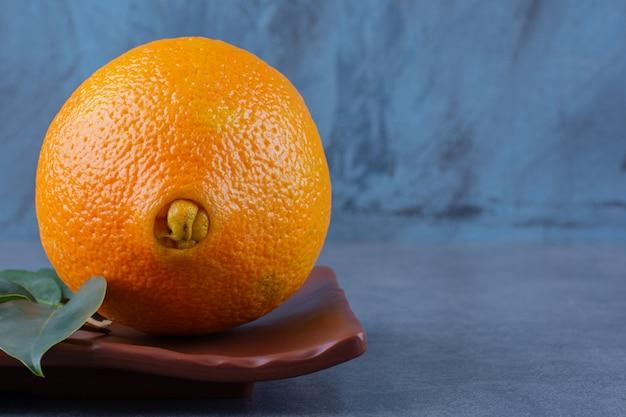 Листья и сочные апельсины на деревянной тарелке, на темной поверхности
