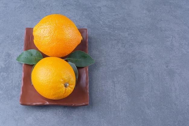 어두운 표면에 나무 접시 접시에 나뭇잎과 달콤한 오렌지
