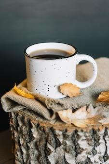 Leaves and mug on cloth and stump