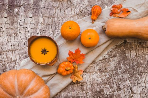 スープの近くの葉とオレンジの果物