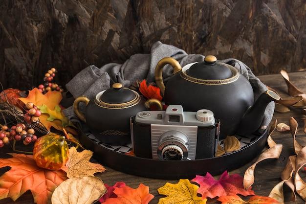 Leaves around tea set and camera