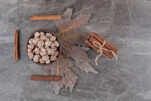 Foglie, dolciumi e cinnamons, sulla superficie del marmo