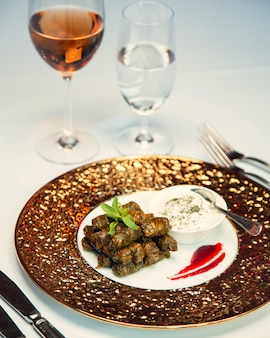 Leaves dolma in plate with sour cream