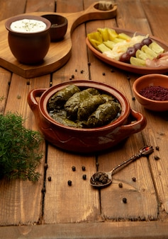 Leaves dolma in pot with side pickles