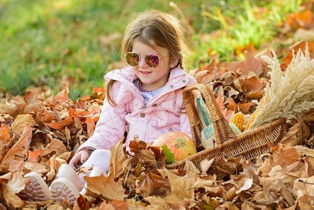 Leaves falling. cute child girl having fun in autumn park. autumn kids fashion.