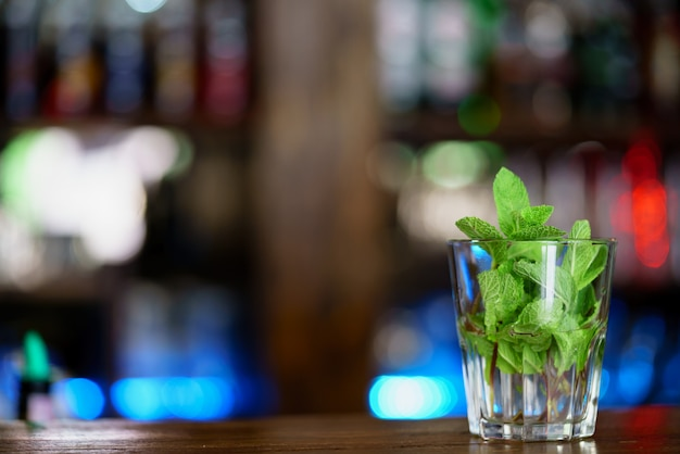 Leaves of fresh mint are in a glass for preparation of a drink on the table