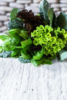 Leaves of green and red lettuce, kale, spinach, amaranth on white table with stone background