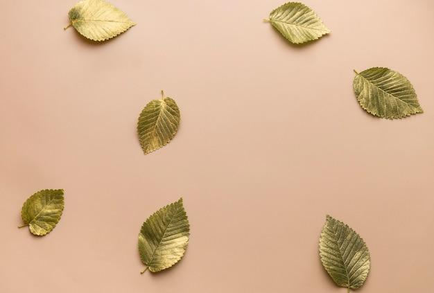Листья в золотой краске на бежевом фоне осенняя концепция вид сверху осенних листьев с золотом