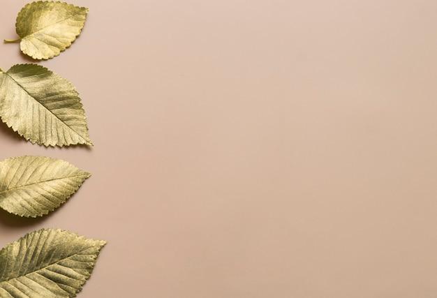 Листья в золотой краске на бежевом фоне с горизонтальной полосой слева осенний концепт топ v ...