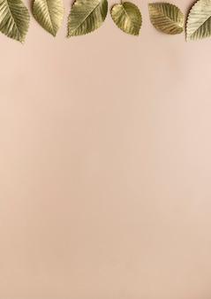 Листья в золотой краске на бежевом фоне с полосой по горизонтали сверху осенней концепции