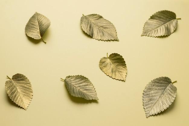 Листья в золотой краске на желтом фоне осенняя концепция вид сверху осенних листьев в золотой боли
