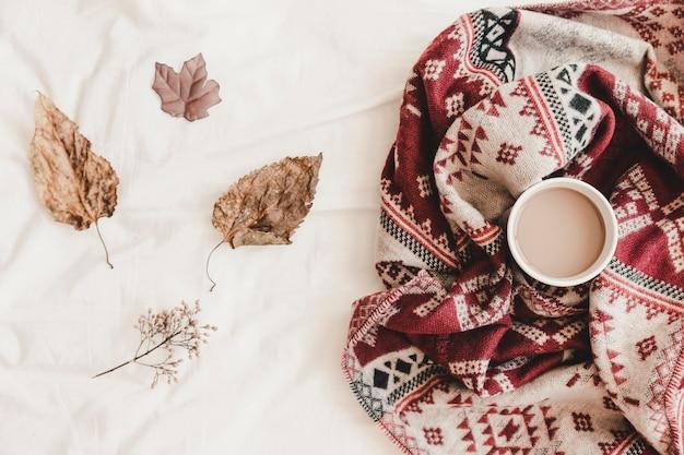 Листья возле горячего напитка в плед на простыне
