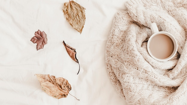 Leaves near hot drink in plaid on bedsheet