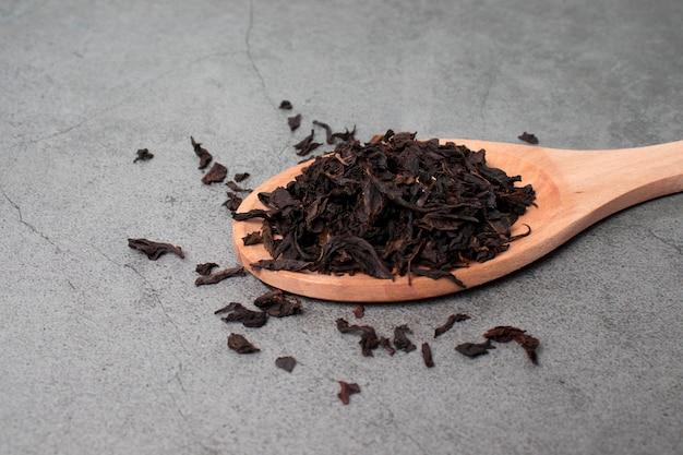 木のスプーンに黒ドライティーの葉のクローズアップ。健康的な天然茶のコンセプト。