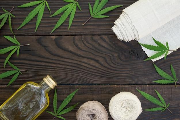 Листья конопли, бутылка конопляного масла и клубки ниток на темной деревянной поверхности