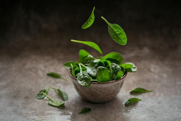 ボウルに新鮮なほうれん草の葉。飛んでいる葉。濃い有機緑色の葉。健康的なビーガンフードライフスタイルの概念