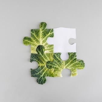 灰色の背景に分離されたパズルとして配置された新鮮な緑のケールの葉。コピースペースのある正方形のレイアウト。フラットレイ