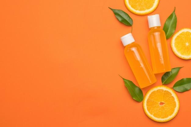 Листья, дольки апельсина и бутылки апельсинового сока на оранжевом фоне. место для текста. концепция терапии натуральными средствами. плоская планировка.