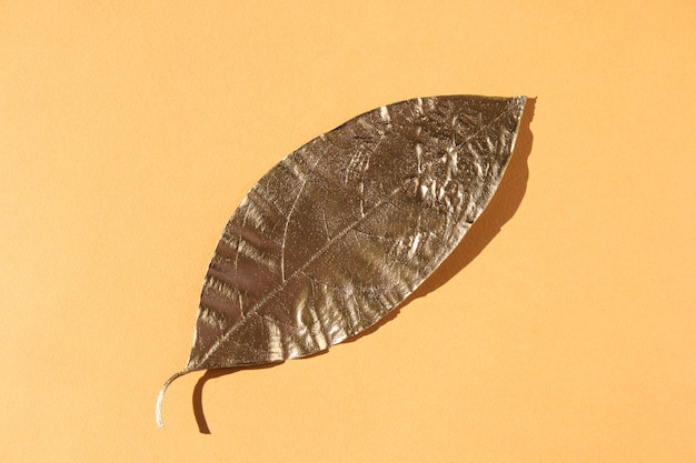 Leaves painted in gold on an orange background. golden autumn concept.