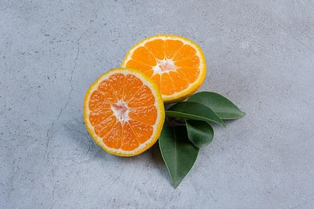 Foglie e fette di mandarini impacchettati insieme su fondo di marmo.