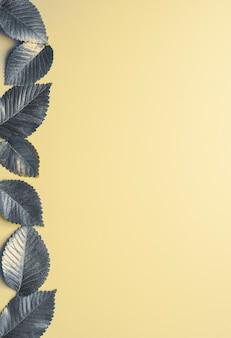 Листья окрашены в серый тренд года на желтом фоне осенняя концепция вид сверху серого