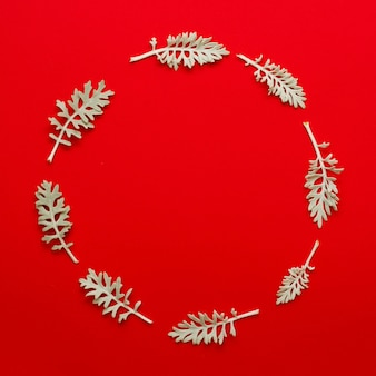 Leaves twig arranged in circular frame on bright red background