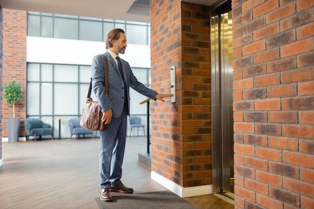 Выход из бизнес-центра. стильный зрелый бородатый бизнесмен, покидающий бизнес-центр вечером