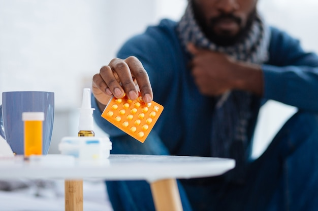 Leaving pills. calm ill person putting a package of pills on the little white table before going to bed