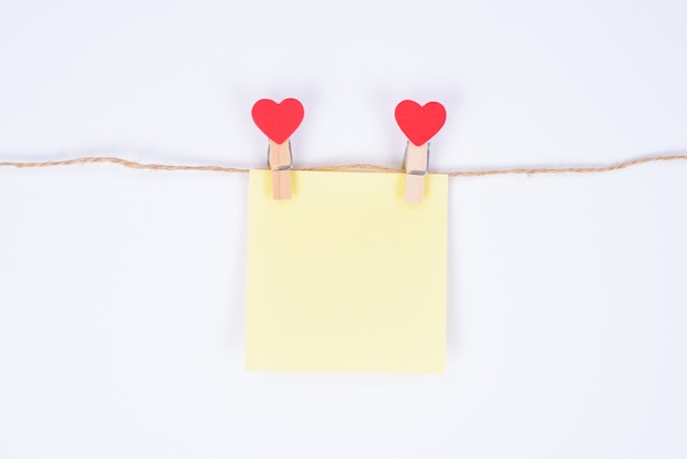 Leaving secret congrats concept. close up photo of small yellow paper sticker hanging on a rope attached with heart shaped clothespins isolated white background