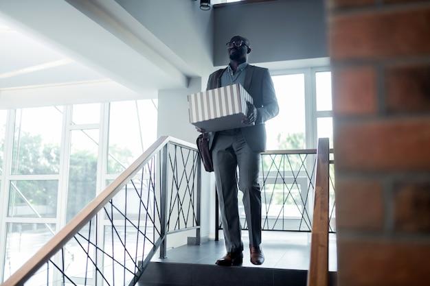 Выходя из офиса. офисный работник в костюме выходит из офиса со своей коробкой после увольнения