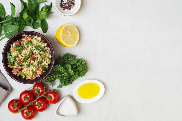 Традиционный ливанский салат табуле из булгура и петрушки, мяты, лимона, помидоров, оливкового масла, соли и перца, вид сверху