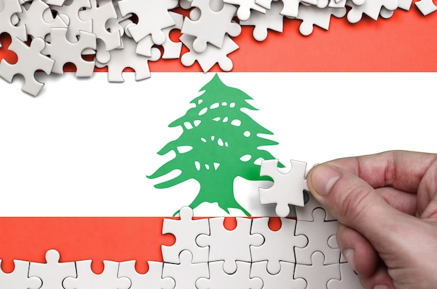 Lebanon flag  is depicted on a table on which the human hand folds a puzzle of white color