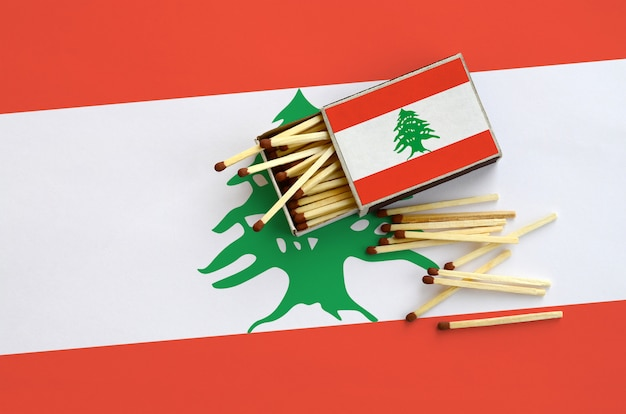 Lebanon flag  is shown on an open matchbox, from which several matches fall and lies on a large flag