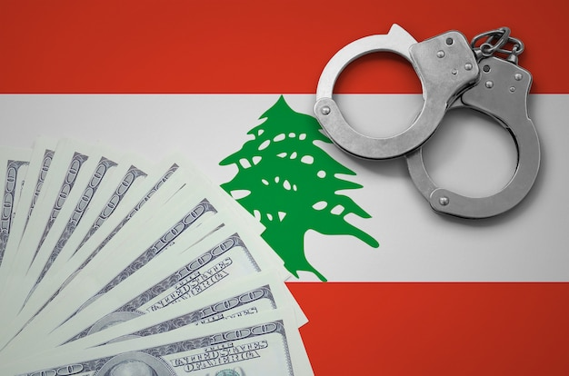 Lebanon flag  with handcuffs and a bundle of dollars. the concept of illegal banking operations in us currency
