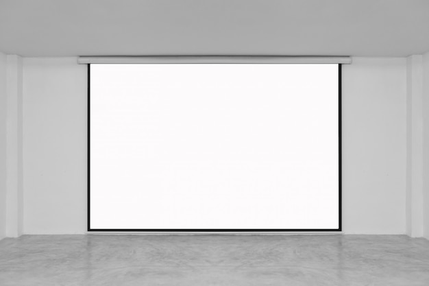 Lecture room with empty white projector screen