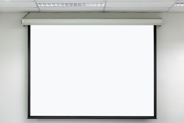 Lecture room with empty white projector screen.