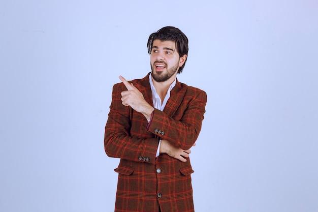 Un docente in giacca marrone che punta a sinistra e ne parla con emozione.
