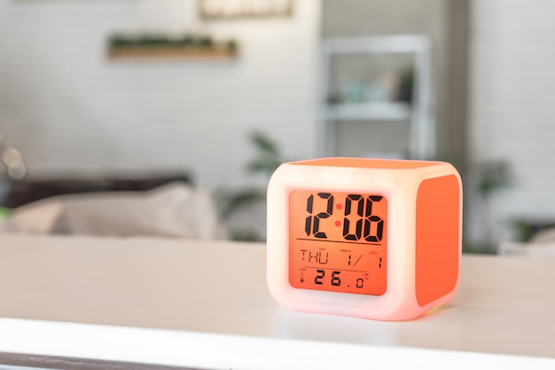 Led alarm clock standing on table background. digital timer display.