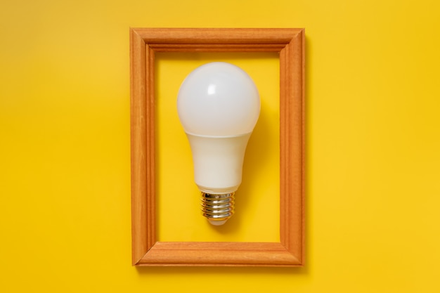 Led energy saving bulb in wooden frame on yellow background
