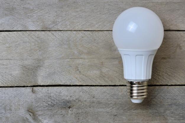 Светодиодная лампа на деревянном столе. копировать пространство