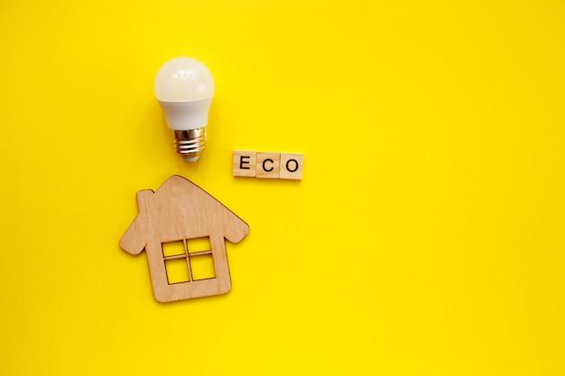 Светодиодная лампочка и деревянный домик на желтом