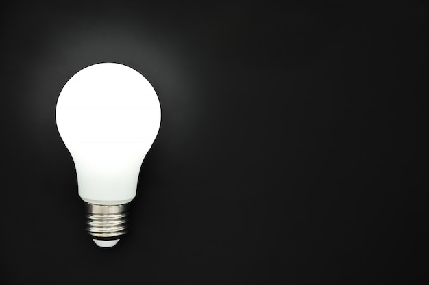 Led light bulb on black background, concept of ideas, creativity, innovation or saving energy, copy space, top view, flat lay