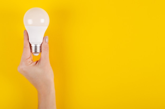 Led light bulb composition on yellow background.